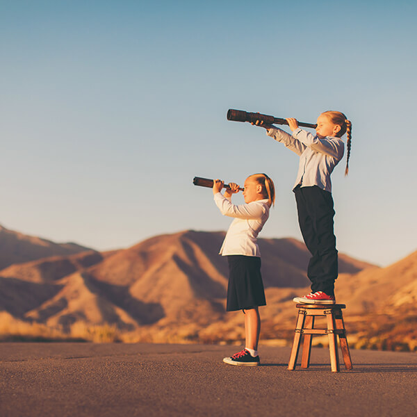 A young business girl or student dressed in business attire stands on a stool looking through a telescope. She is searching for her next big opportunity to prove her success and abilities. She is confident looking in the mountains of Utah, USA.